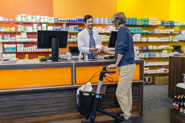 Pharmacist giving medicine to customer with wheeled walker in pharmacy - MFF04280