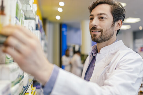 Pharmacist taking medicine from shelf in pharmacy - MFF04283