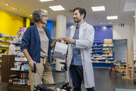 Pharmacist giving bag of medicine to customer with wheeled walker in pharmacy - MFF04286
