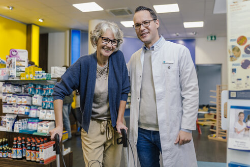 Portrait of smiling pharmacist and customer with wheeled walker in pharmacy - MFF04289