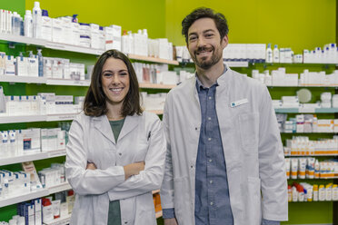 Portrait of two smiling pharmacist at shelf with medicine in pharmacy - MFF04292