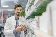 Portrait of smiling pharmacist with cream jar at shelf in pharmacy - MFF04295