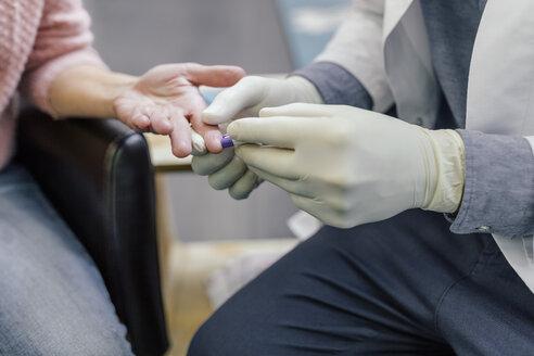 Pharmacist measuring blood sugar of customer in pharmacy - MFF04298