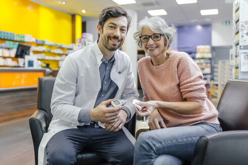 Portrait of smiling pharmacist and customer with blood sugar meter in pharmacy - MFF04301