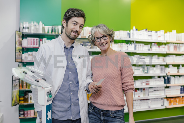 Portrait of smiling pharmacist with customer at sclaes in pharmacy - MFF04304 - Mareen Fischinger/Westend61