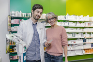Portrait of smiling pharmacist with customer at sclaes in pharmacy - MFF04304