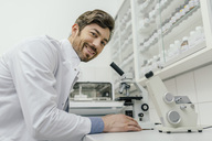 Portrait of smiling man using microscope in laboratory - MFF04307
