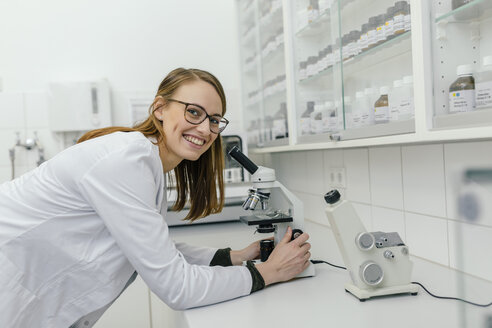 Portrait of smiling woman using microscope in laboratory - MFF04310