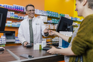 Customer paying cashless in a pharmacy - MFF04322