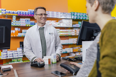 Pharmacist explaining medicine to customer in pharmacy - MFF04325