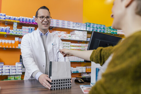 Pharmacist giving bag with medicine to customer in pharmacy - MFF04328