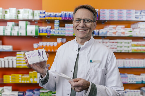 Portrait of smiling pharmacist holding tablet package and prescription in pharmacy - MFF04334