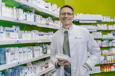Portrait of smiling pharmacist holding medicine in pharmacy - MFF04337