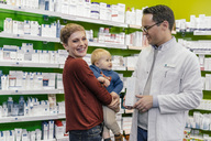 Pharmacist advising mother with son in pharmacy - MFF04343