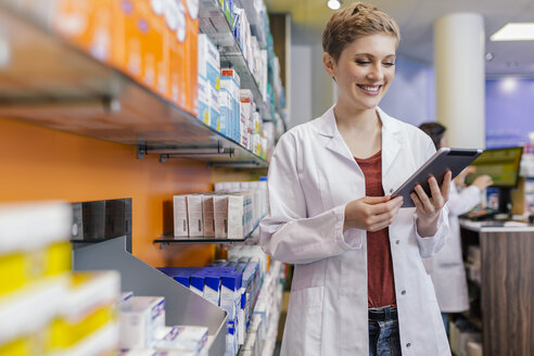 Smiling pharmacist at shelf with medicine in pharmacy holding tablet - MFF04346