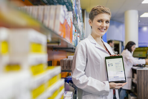 Portrait of smiling pharmacist in pharmacy holding tablet with digital order - MFF04349