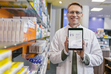 Portrait of smiling pharmacist in pharmacy holding tablet with digital order - MFF04352