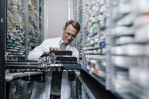 Pharmacist examining commissioning machine in pharmacy - MFF04358