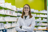Portrait of smiling pharmacist at shelf with medicine in pharmacy - MFF04367