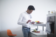 Man standing in kitchen reading recipe on his digital tablet - SGF02141