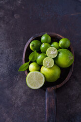 Wooden spoon with sliced and whole limequats, limes and leaves on rusty ground - CSF28696