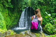 Costa Rica, Woman looking at a waterfall on the Cerro Chato route - KIJF01846