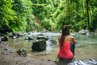Costa Rica, Arenal Volcano National Park, Woman sitting on a stone of the river Fortuna - KIJF01855