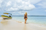 Panama, Bocas del Toro, Cayo Zapatilla, Woman from behind on beach with a moored boat - KIJF01870