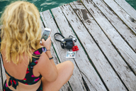 Panama, Bocas del Toro, Woman taking a picture with her smartphone of a camera and instant photographs - KIJF01876
