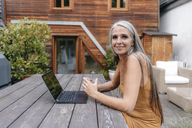 Portrait of smiling woman sitting on terrace of her house with laptop and glass of water - KNSF03460