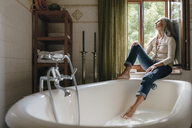Woman sitting on window sill in the bathroom looking out of window - KNSF03463
