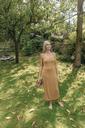 Woman standing barefoot in the garden relaxing - KNSF03466