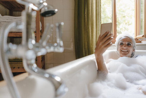 Portrait of happy woman in bathtub taking selfie with cell phone - KNSF03469