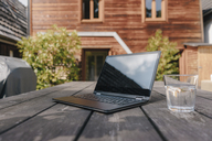 Laptop and glass of water on table on terrace - KNSF03475