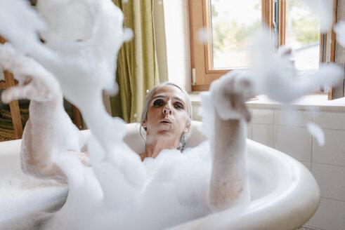 Portrait of woman in bathtub playing with foam - KNSF03484