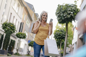 Smiling woman on the street carrying shopping bags looking at cell phone - KNSF03490