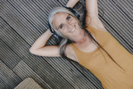 Portrait of happy woman lying on terrace listening music with headphones - KNSF03493