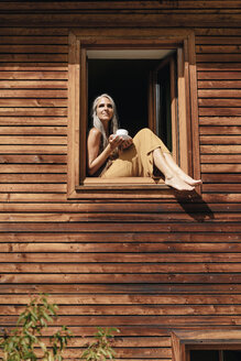 Woman with cup of coffee sitting on window sill of her house sunbathing - KNSF03499
