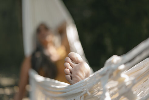 Foot of woman relaxing in hammock in the garden, close-up - KNSF03505