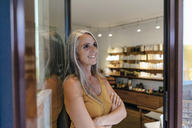 Portrait of smiling businesswoman at entrance of her shop - KNSF03514