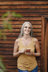 Portrait of happy mature woman with coffee cup in front of wooden facade - KNSF03523