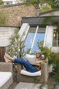 Woman relaxing on terrace using laptop - KNSF03529