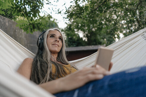 Portrait of woman with cell phone lying in hammock in the garden listening music with headphones - KNSF03541