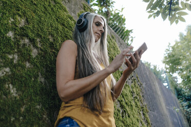 Woman with cell phone standing in the garden listening music with headphones - KNSF03544