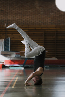 Young man doing a headstand in gym - OCAF00006
