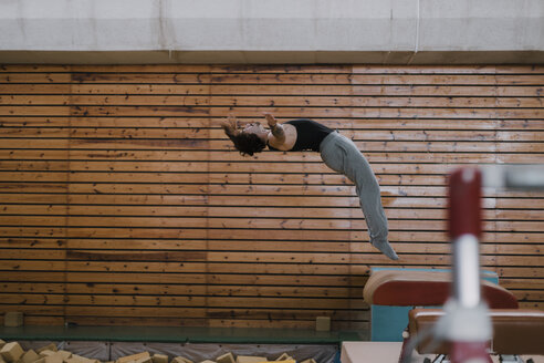 Gymnast exercising at vaulting table in gym - OCAF00009