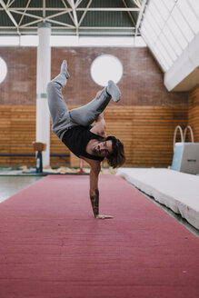 Young man doing acrobatic exercise in gym - OCAF00015