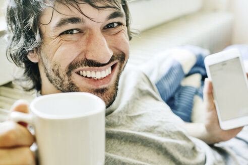 Portrait of laughing young man lying on bed with smartphone and cup of coffee - JATF00975