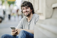 Portrait of smiling young man with cell phone outdoors - JATF00978