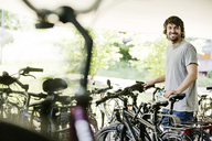 Portrait of smiling young man parking his bicycle - JATF00984